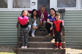 family poses for a front porch portrait as part of the Wethersfield PEP program