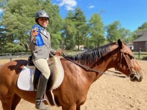 A girl on a bay horse smiling and holding up a blue first place ribbon at a horse show