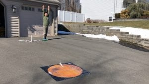 boy with hands over his head and excited expression on his face while toy rocket lies on mars map in his driveway