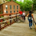 bikers and woman walking a dog on a bridge