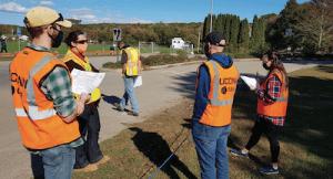 group of people in orange vests and masks looking at landscape