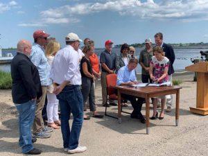 Gov. Lamont signs the Shellfish Restoration Bill on July 23 as legislators and industry members look on